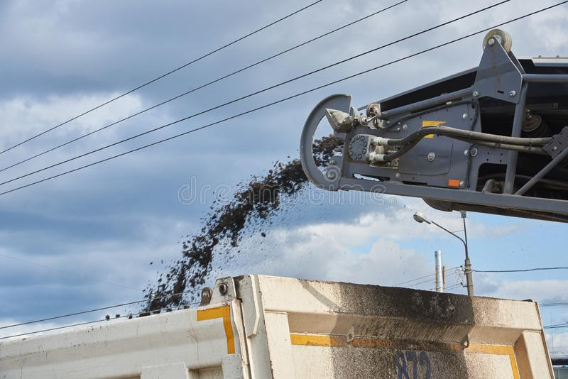 Loading old asphalt onto a dump truck. Road repair work. Loading old asphalt onto a dump truck.  Road repair work royalty free stock images