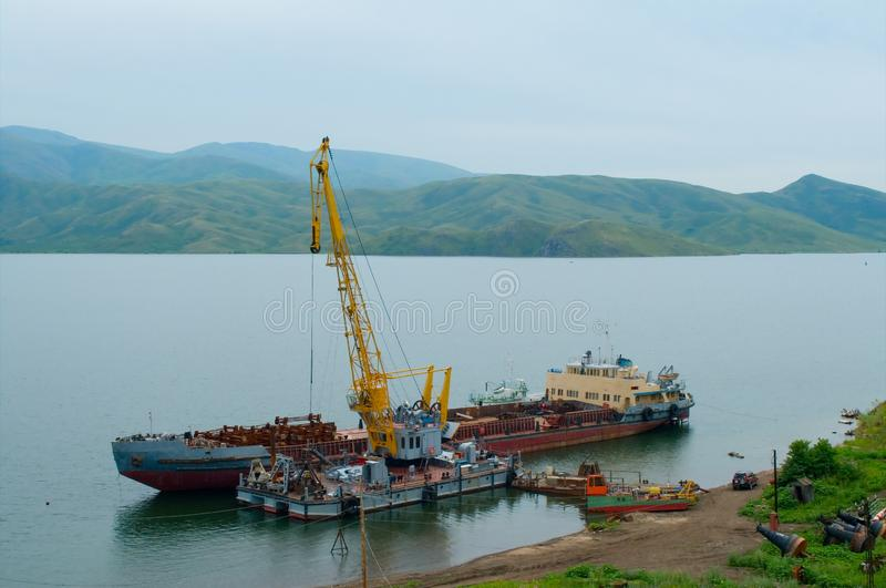 Loading of scrap metal onto a cargo ship. Irtysh River, East Kazakhstan Region of Kazakhstan stock photos