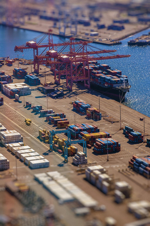 Loading a transport ship with cargo, containers, with tilt-shift lens effect. From bird's eye perspective royalty free stock photography