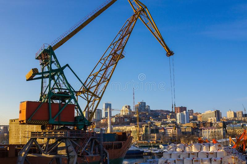 Loading work in the port. A cargo terminal in the port, a crane works. Loading of goods on the ship, sea freight. Bright blue sky, in the distance city royalty free stock photography