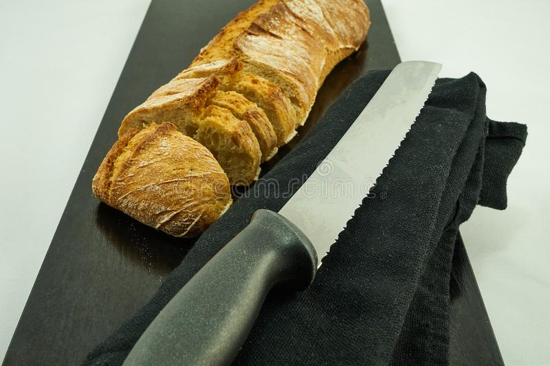 A loaf of bread cut next to a metal knife to cut bread. The knife is on a black kitchen cloth. The bread is on top of a black wooden board on a white stock images