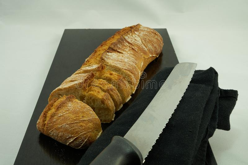 A loaf of bread cut over a black wooden board and a bread knife. The black wooden table is located on a white background royalty free stock photo