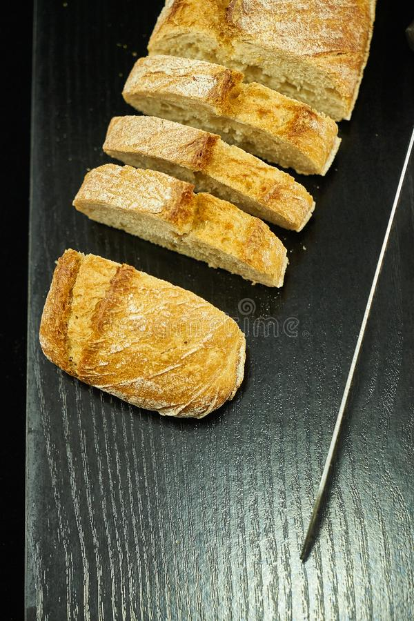 A loaf of bread cut over a black wooden board next to a metal bread knife. The black wooden table is located on a white background stock photos