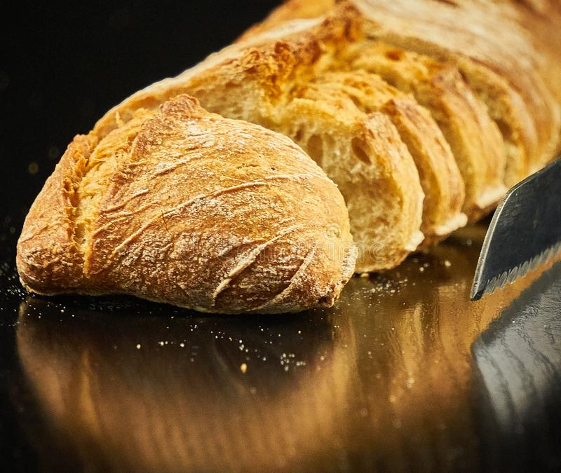 A loaf of bread cut over a black wooden board next to a metal bread knife. The black wooden table is located on a white background stock images