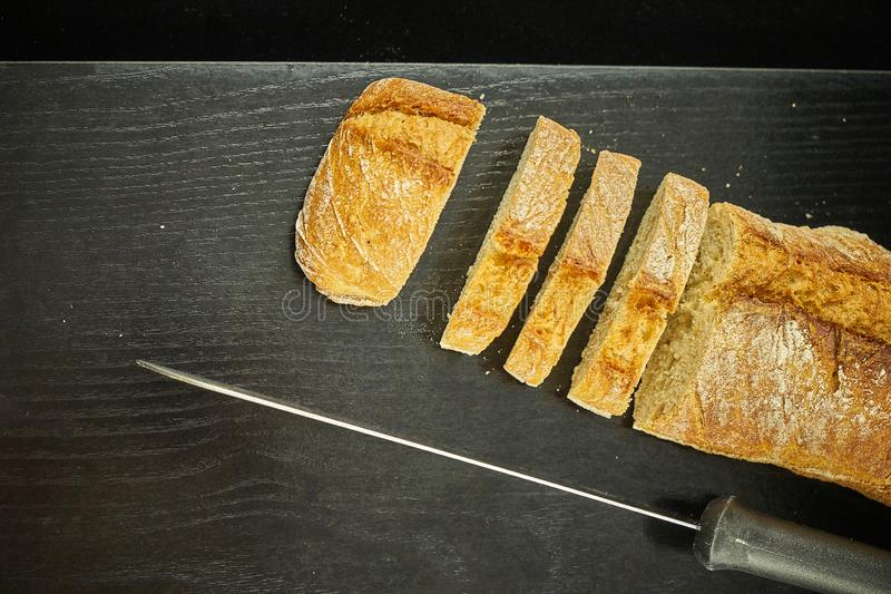 A loaf of bread cut over a black wooden board next to a metal bread knife. The black wooden table is located on a white background stock photography