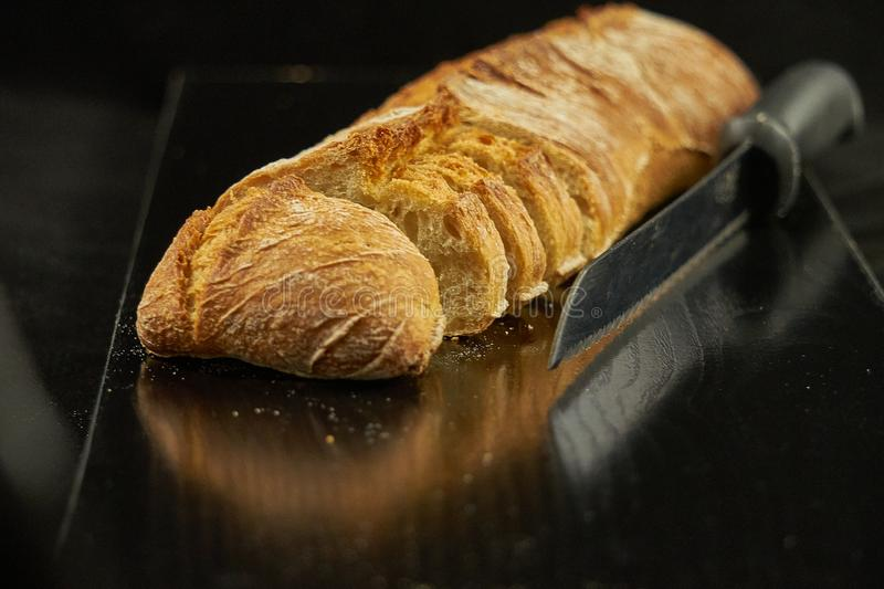 A loaf of bread cut over a black wooden board next to a metal bread knife. The black wooden table is located on a white background royalty free stock image