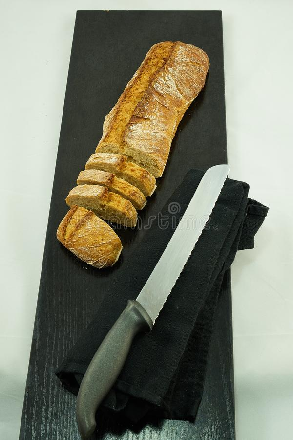 A loaf of bread cut on top of a black wooden board, next to a bread knife. The knife is located on top of a black kitchen cloth. The whole set is  in the royalty free stock photo
