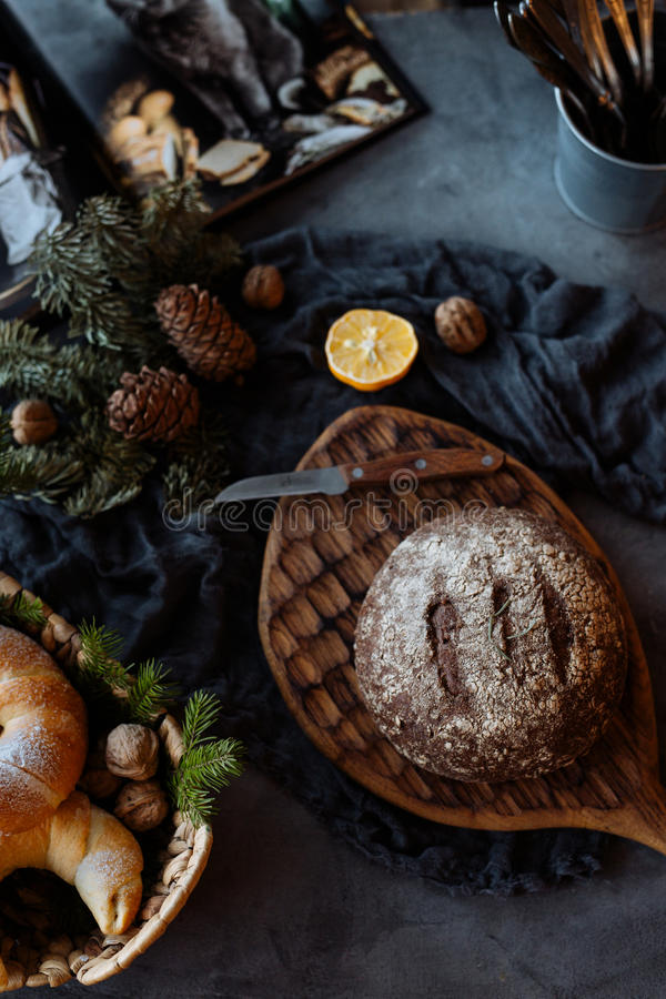 Loaf of bread and knife on a table. Fresh loaf of bread and knife on beautifully decorated table royalty free stock images