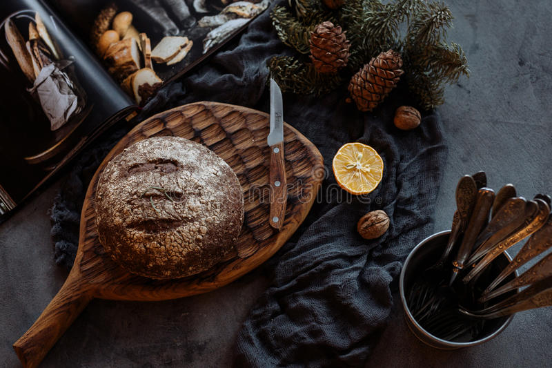 Loaf of bread and knife on a table. Fresh loaf of bread and knife on beautifully decorated table royalty free stock image