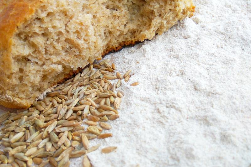 Loaf of fresh baked wheat and rye bread with grains and white flour on wooden table background royalty free stock images