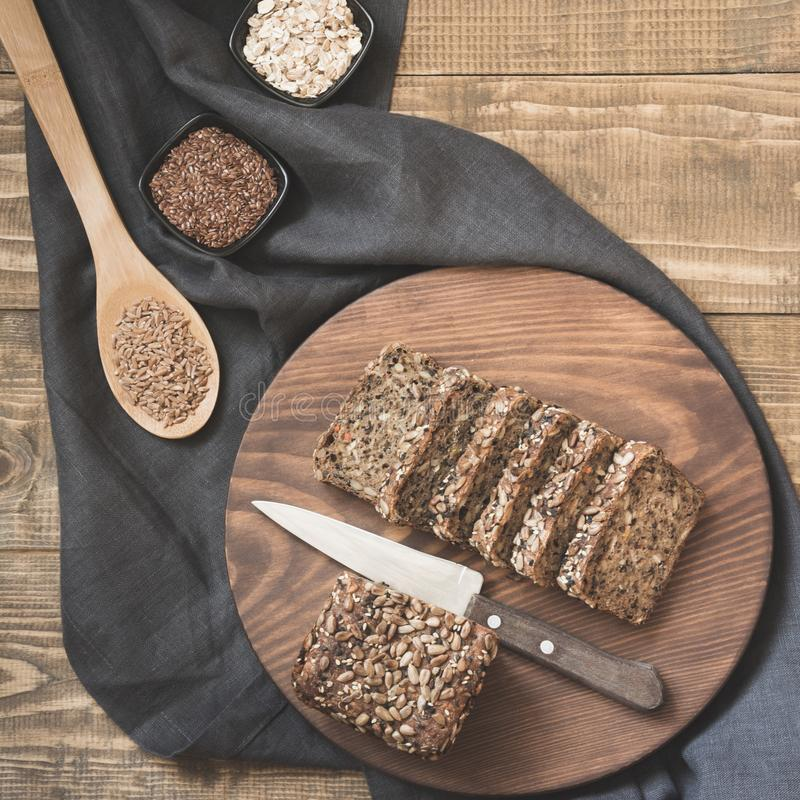 A loaf of fresh rustic whole rye bread with ingredients in bowl on wooden board, rural background. Top view. Copy space. stock photo