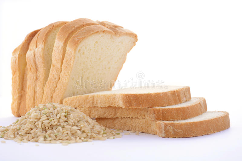 Loaf Rice Sourdough bread with raw brown rice. Loaf of sliced gluten-free rice sourdough bread with pile of raw brown rice on white table royalty free stock photo