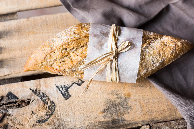 Loaf of rye whole wheat bread wrapped in parchment paper on linen napkin, plank wood background stock images