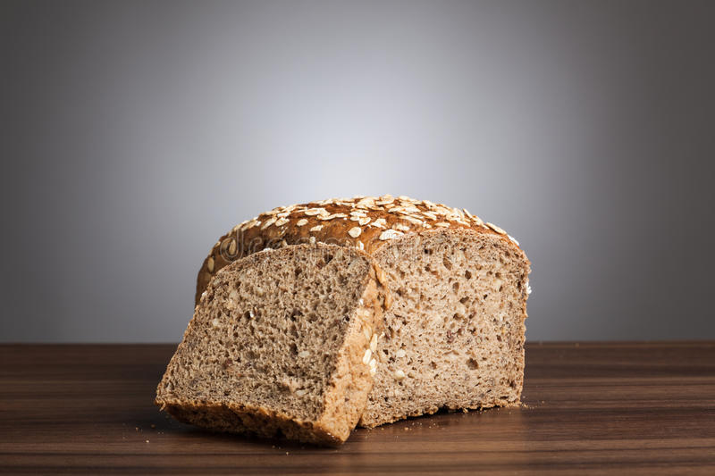 Loaf and slice of wholemeal bread on table