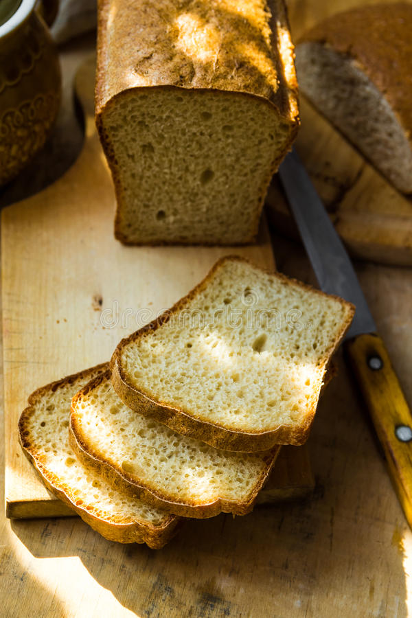 Loaf of sourdough bread cut into slices on wood cutting board, knife, kitchen table, sunlight flecks, cozy stock images