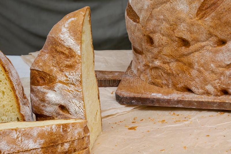 Loaf of traditional rustic bread on cutting board and cut slices of bread stock images