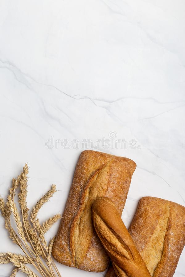 Loaf of bread with ear of wheat on white royalty free stock images