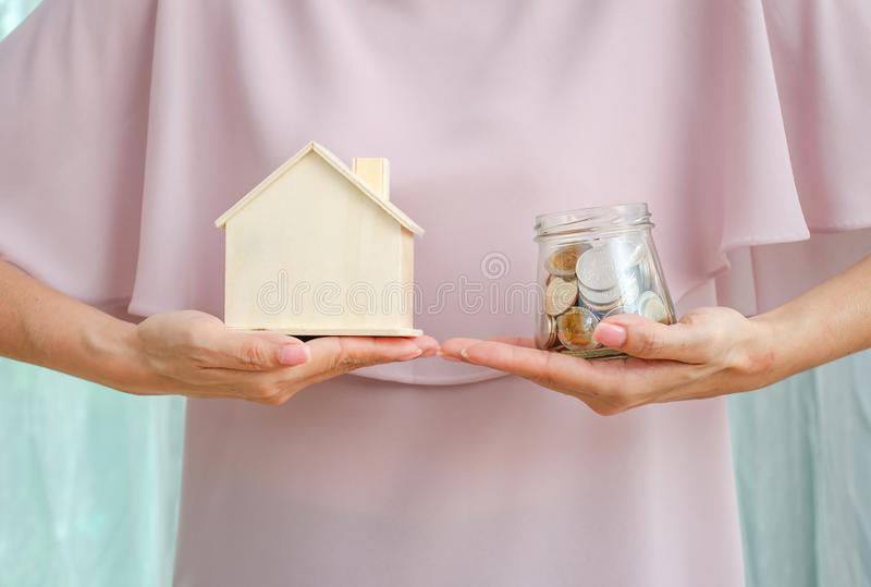Loan or save for buy a house and real estate concept, Woman hand holding money  in glass jar and a model home stock images