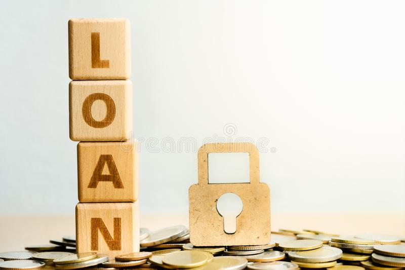 Loan on wooden surface and Wooden lock stack of coins in concept of savings. stock photos