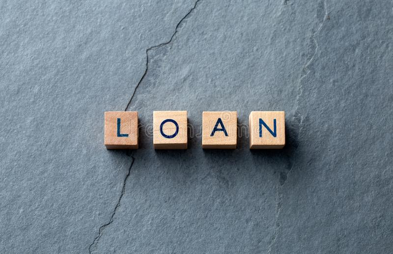 LOAN word on wooden blocks on slate base royalty free stock images