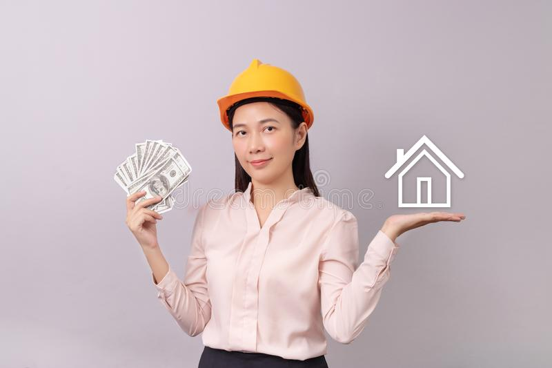 Loans for real estate concept, woman with yellow helmet holding banknote money in hand and white logo home icon in another hand royalty free stock image