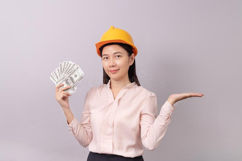 Loans for real estate concept, woman with yellow helmet holding banknote money in right hand and open the empty palm. Of the left hand royalty free stock image