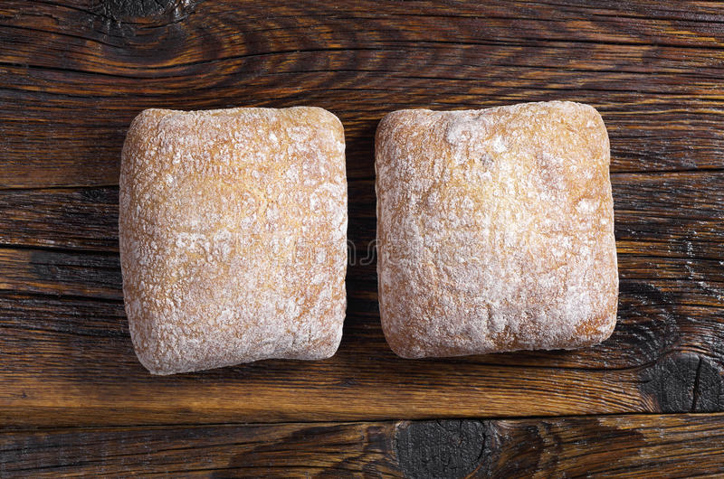 Loaves of bread ciabatta. Small loaves of bread ciabatta on dark wooden background, top view royalty free stock photography