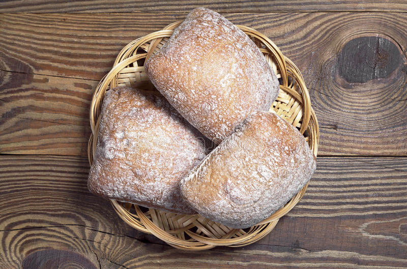 Loaves of bread ciabatta. Small loaves of bread ciabatta in wicker plate on wooden background, top view stock image