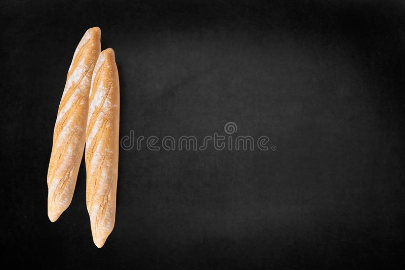 Loaves of bread on dark board, top view free text space. royalty free stock images