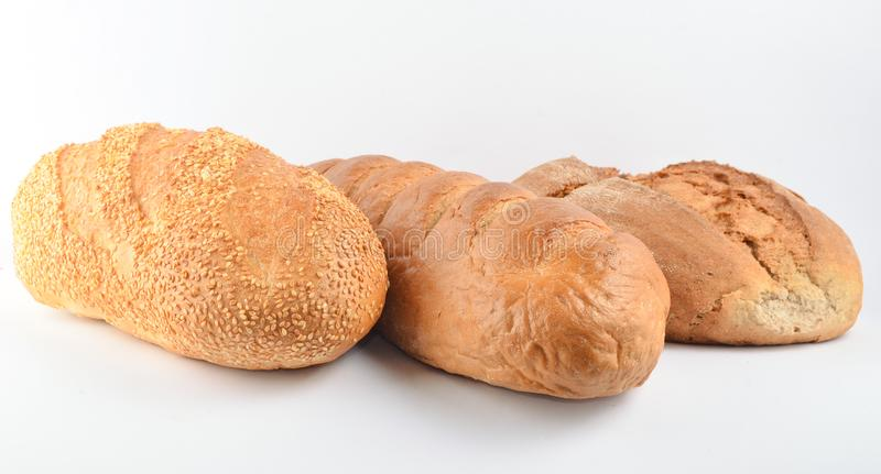 Loaves of bread isolated on white background. Wheat, rye, bread with sesame seeds royalty free stock images