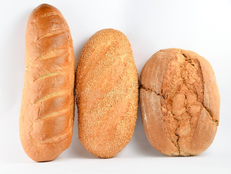 Loaves of bread isolated on white background. Wheat, rye, bread with sesame seeds royalty free stock photo