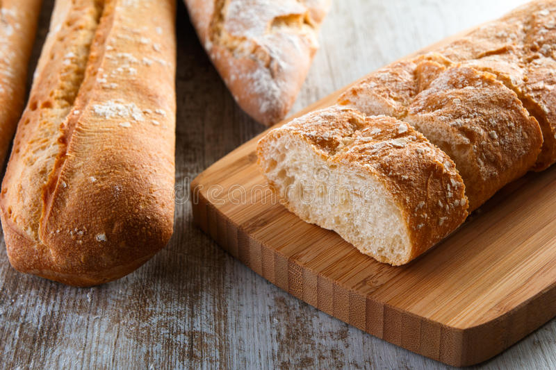 Loaves of bread on work table. Loaves of bread cut on slides an place on a work table stock image