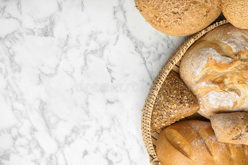 Loaves of different breads on white marble background. Space for text. Loaves of different breads on white marble background, flat lay. Space for text stock photography