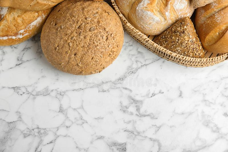 Loaves of different breads on white marble background, flat lay. Space. For text stock photo