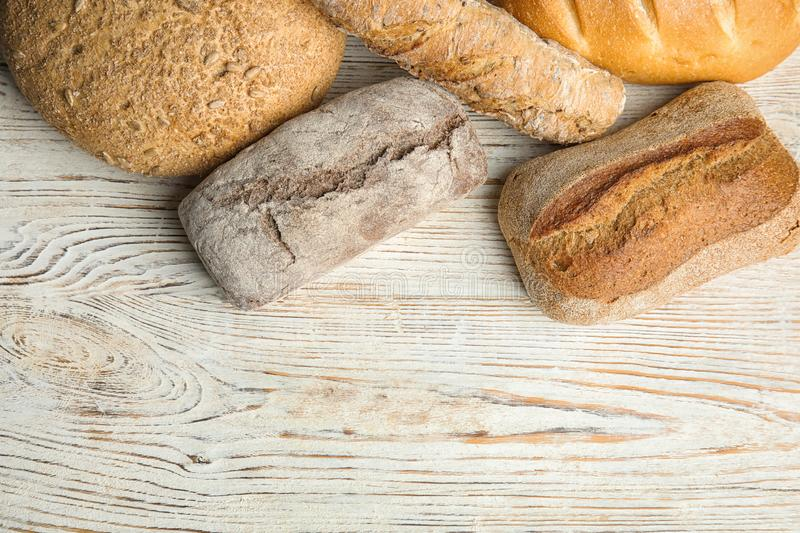 Loaves of different breads on white wooden background. Space for text royalty free stock image