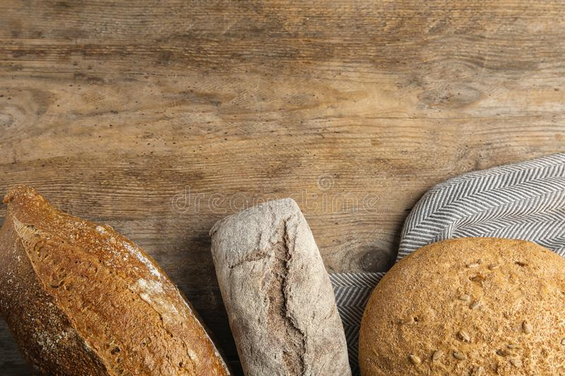 Loaves of different breads on wooden , flat lay. Space for text stock images