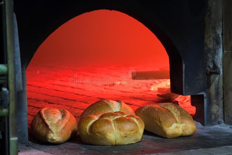 Loaves of fresh baked bread in front of oven with fire inside, advertising photo royalty free stock photo