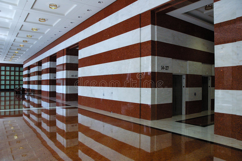 Lobby in Marble. A lobby of a large skyscraper, with Marble adorned walls and floor. True Luxury royalty free stock image