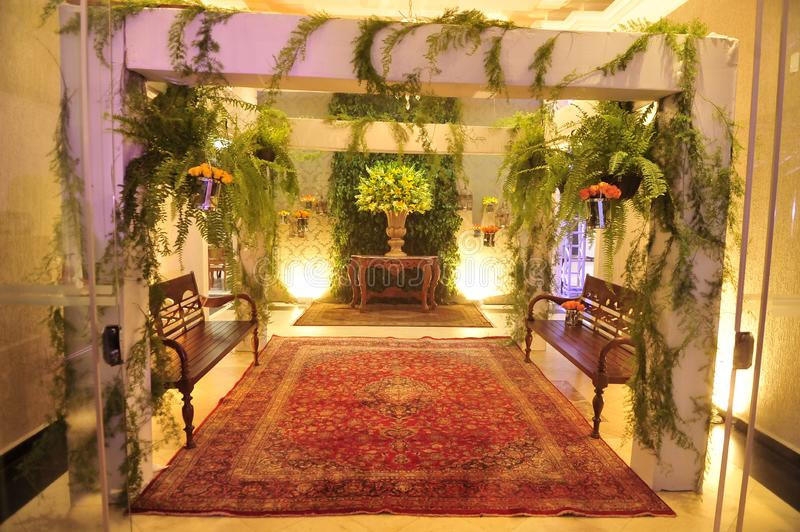 Lobby with red carpet and yellow-lighted flower arrangements.  stock photos