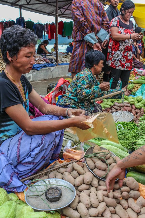 Lobesa Village, Punakha, Bhutan - September 11, 2016: Unidentified people at weekly farmers market. Fresh fruits and vegetables for sale at the local market stock image