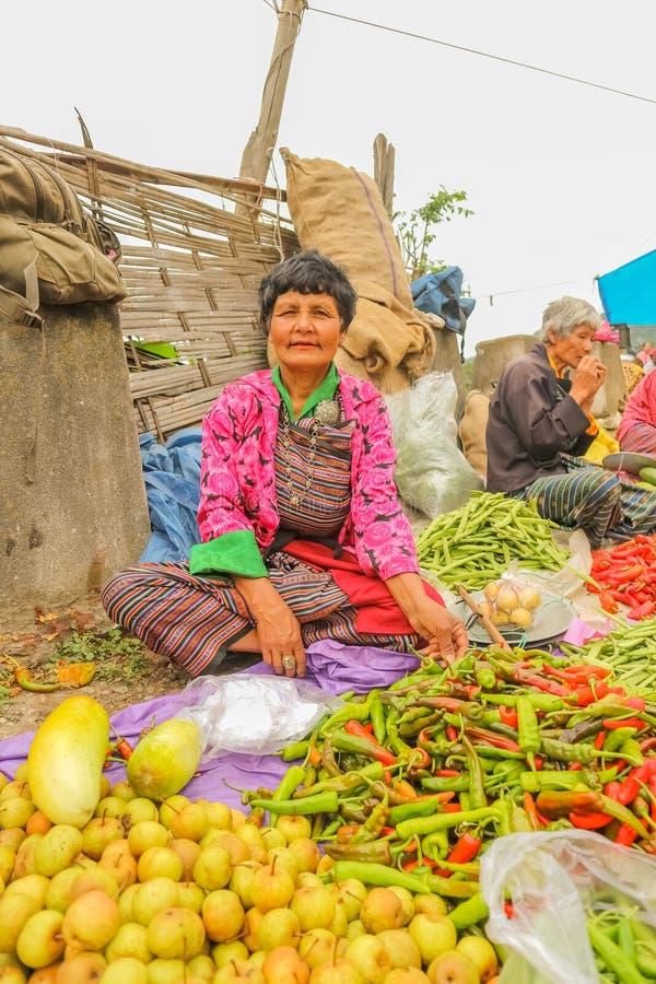 Lobesadorp, Punakha, Bhutan - September 11, 2016: Niet geïdentificeerde glimlachende vrouw bij wekelijkse landbouwersmarkt stock afbeeldingen