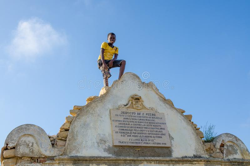LOBITO, ANGOLA - 9 DE MAIO DE 2014: Menino africano não identificado com a camisa amarela que está no forte de Pedro Portuguese d fotos de stock royalty free
