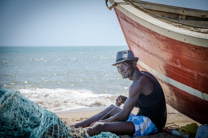 LOBITO, ANGOLA - 9. MAI 2014: Nicht identifizierter angolanischer Fischer, der vor rotem Fischerboot an den Strandfestlegungsnetz stockbild