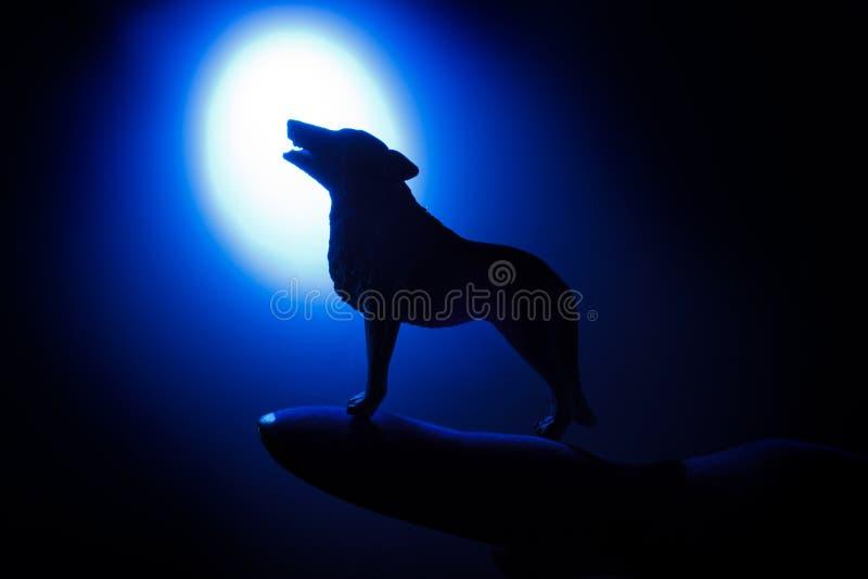 Lobo en silueta que grita a la Luna Llena fotografía de archivo libre de regalías