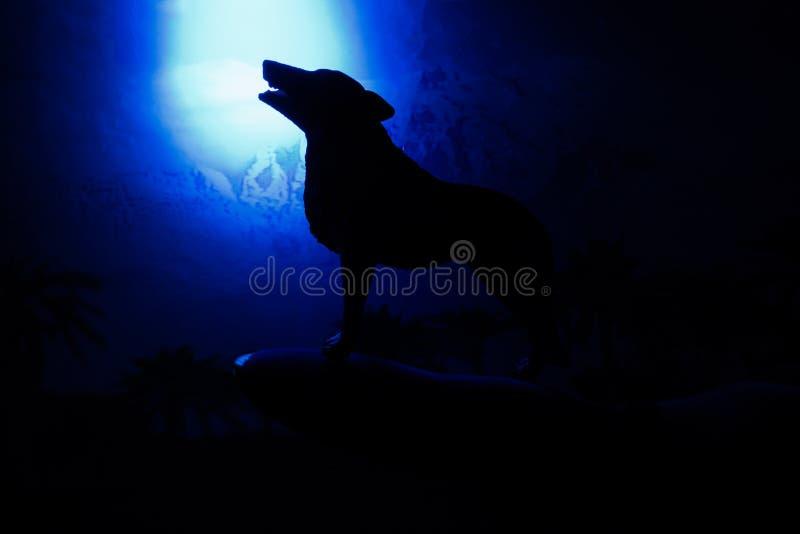 Lobo en silueta que grita a la Luna Llena fotografía de archivo