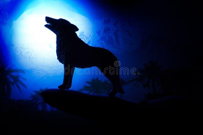 Lobo en silueta que grita a la Luna Llena imagen de archivo libre de regalías