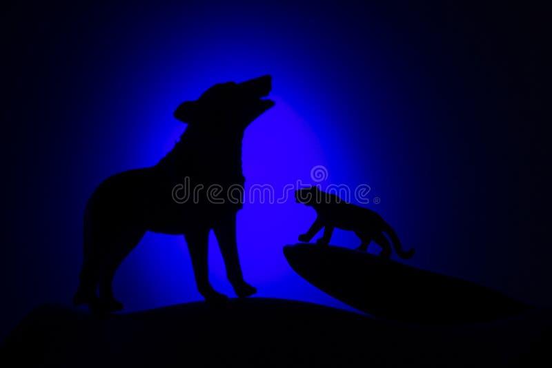 Lobo en silueta que grita a la Luna Llena imagen de archivo