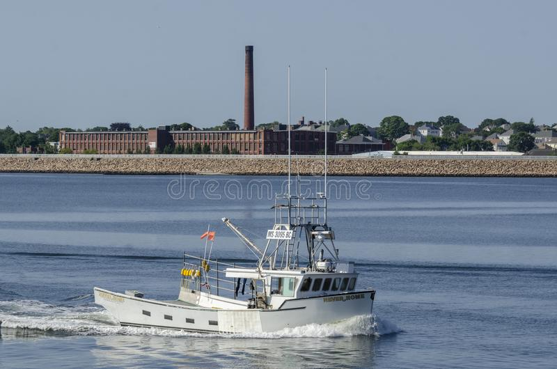 Lobster boat Never Home with New Bedford in background. Fairhaven, Massachusetts, USA - August 5, 2018: Lobster boat Never Home returning to port on summer royalty free stock photography