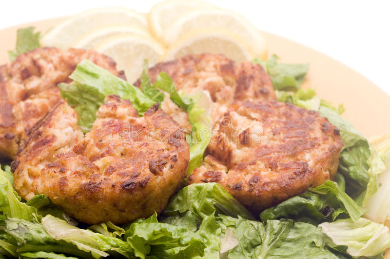 Lobster cakes bed of lettuce with lemon slice wedges royalty free stock photo