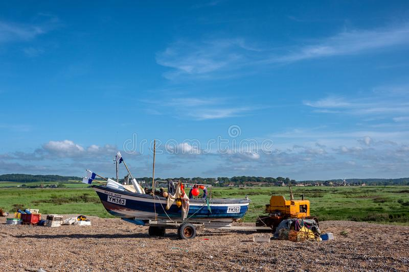 A Fisherman on a Shingle Beach. The lobster/crab boat Blue Boy catches the early evening sun. Cley Windmill seen in the distance. The shingle beach at Cley next stock photos